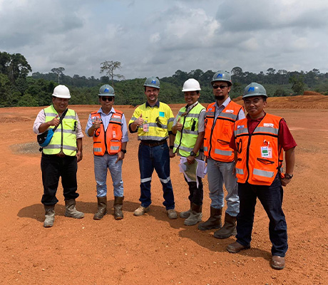 Satisfied employees and customers standing on cleared land